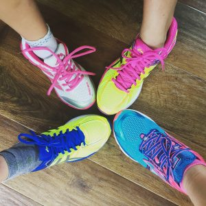 4 individuals' feet with colorful running shoes