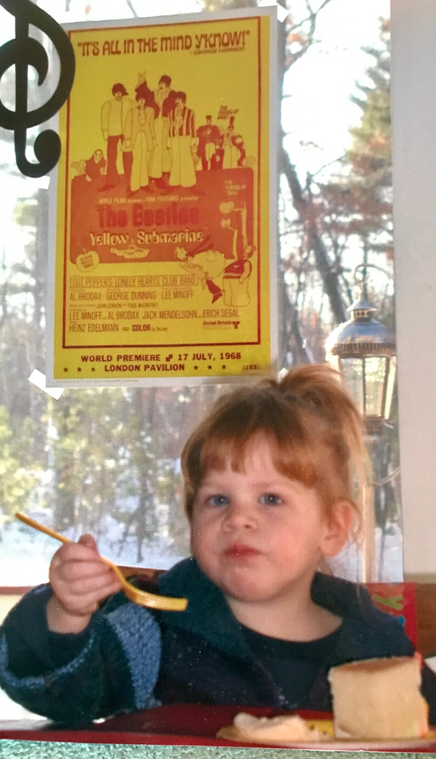 Child eating at table with Yellow Submarine Beatles poster in background